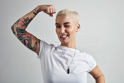 Buy stock photo Shot of an attractive young woman flexing her biceps against a grey background
