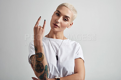 Buy stock photo Portrait of an attractive young woman showing the rock on sign against a grey background
