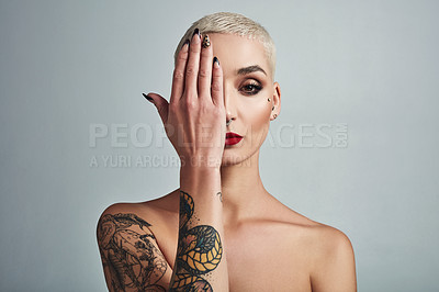 Buy stock photo Portrait of an attractive young woman covering half her face with her hand against a grey background