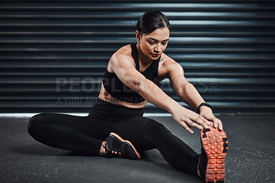 Buy stock photo Shot of a sporty young woman stretching against a dark background