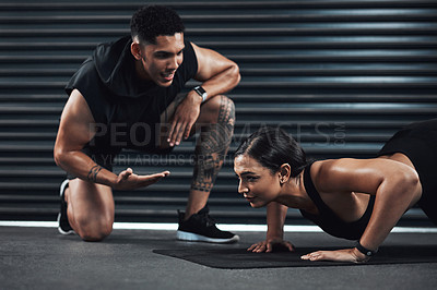 Buy stock photo Shot of a fitness trainer assisting a young woman doing pushup exercises against a dark background
