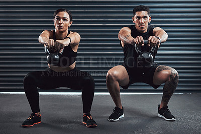 Buy stock photo Shot of two sporty young people exercising together with kettle bells against a dark background