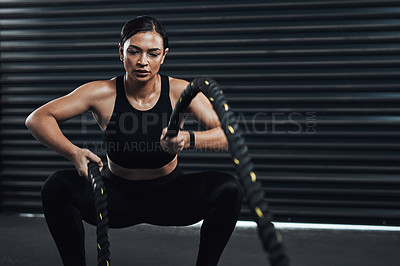 Buy stock photo Shot of a sporty young woman exercising with battle ropes against a dark background