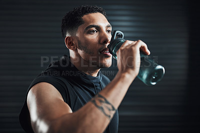 Buy stock photo Shot of a sporty young man drinking water while exercising against a dark background