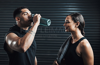Buy stock photo Shot of two sporty young people drinking water while exercising together against a dark background