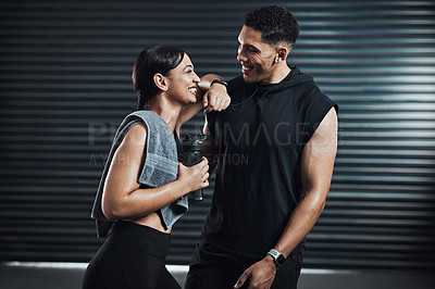 Buy stock photo Shot of two sporty young people taking a break while exercising together