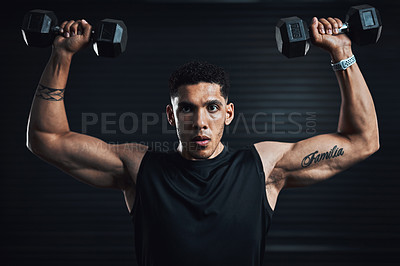 Buy stock photo Shot of a sporty young man exercising with dumbbells against a dark background