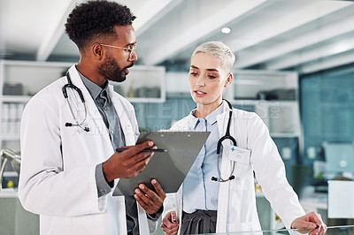 Buy stock photo Shot of two doctors going over paperwork in a hospital