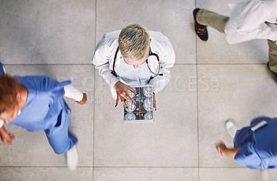 Buy stock photo High angle shot of a doctor looking at x-rays on a digital tablet in a busy hospital