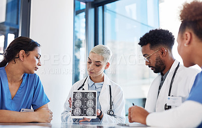 Buy stock photo Shot of a group of medical practitioners analysing x-rays on a digital tablet in a hospital boardroom