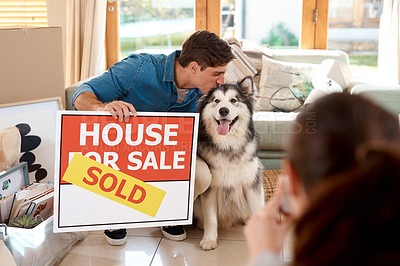 Buy stock photo Shot of a happy young couple and their dog taking photos with a sold sign in their new home
