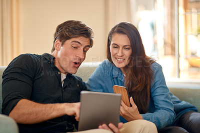 Buy stock photo Cropped shot of a couple using wireless technology while relaxing on the sofa at home