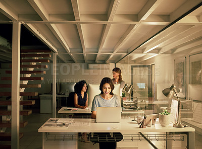 Buy stock photo Cropped shot of an attractive young businesswoman using her laptop while her colleagues work behind her late at night