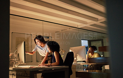 Buy stock photo Cropped shot of two attractive young businesswomen working on a computer together in the office at night