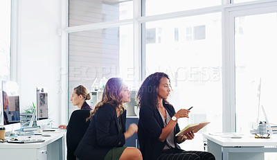 Buy stock photo Shot of two young businesswomen using a computer together in a modern office