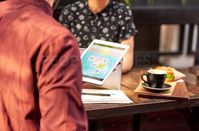 Buy stock photo Shot of two unrecognizable businesspeople using a digital tablet while working together at an outdoor cafe