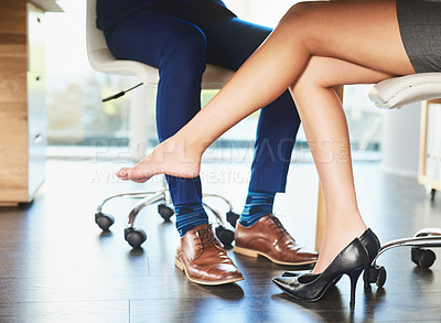 Buy stock photo Cropped shot of an unrecognizable businesswoman seductively rubbing her male coworkers leg with her foot in the office
