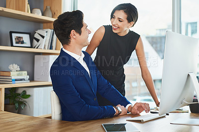 Buy stock photo Cropped shot of two young business coworkers working on a computer together in the office during the day