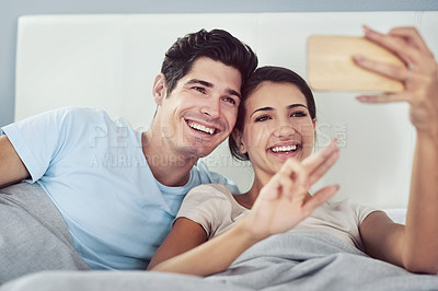 Buy stock photo Shot of an affectionate young couple taking a selfie in their bedroom