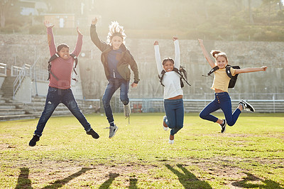Buy stock photo Shot of a group of children jumping for joy on a school field