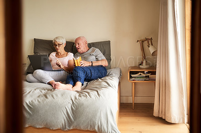 Buy stock photo Shot of an affectionate senior couple reading and spending time together in their bedroom at home