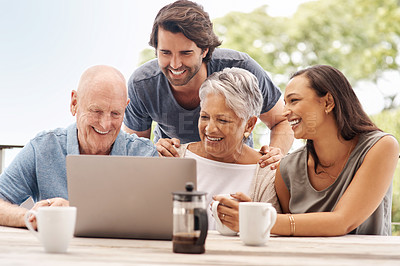 Buy stock photo Shot of a happy family using a laptop together outside at home