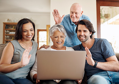Buy stock photo Shot of a happy family waving while using a laptop together outside at home