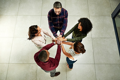 Buy stock photo High angle shot of a diverse group of businesspeople standing and placing their hands in the middle of the circle