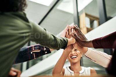 Buy stock photo Cropped shot of a diverse group of businesspeople sitting in the office and doing a group high five