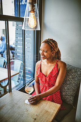 Buy stock photo Shot of an attractive young woman looking cheerful while enjoying a glass of wine at a cafe