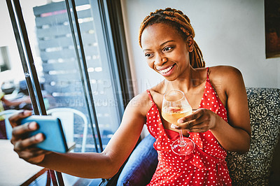 Buy stock photo Shot of an attractive young woman taking selfies with her cellphone while enjoying a glass of wine at a cafe