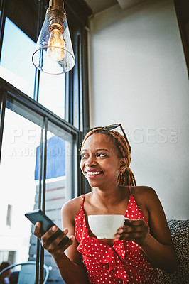 Buy stock photo Shot of an attractive young woman using her cellphone and enjoying a cup of coffee at a cafe