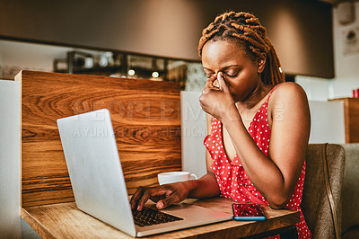 Buy stock photo Shot of an attractive young woman suffering from a headache while working on her laptop inside a cafe