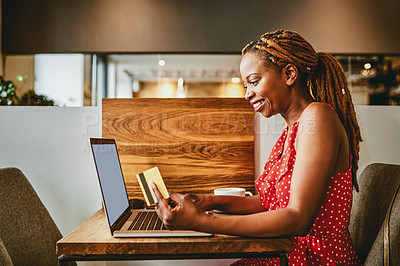 Buy stock photo Shot of an attractive young woman using her credit card and laptop while relaxing inside a cafe