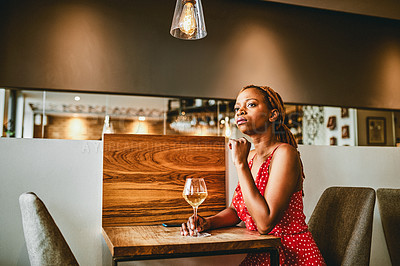 Buy stock photo Shot of an attractive young woman looking thoughtful while enjoying a glass of wine inside a cafe