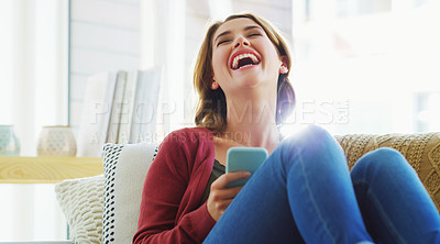 Buy stock photo Cropped shot of an attractive young woman sitting alone on the sofa in her living room and using her cellphone