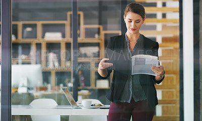 Buy stock photo Cropped shot of an attractive young businesswoman standing alone in her office and reading documents