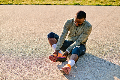 Buy stock photo Shot of a sporty young man suffering from a sports injury outdoors