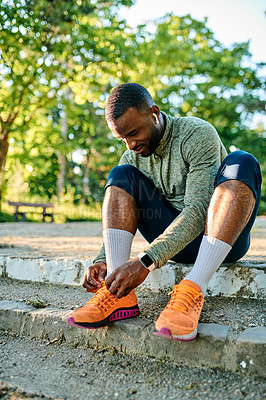 Buy stock photo Shot of a sporty young man tying his shoelaces while out for a run