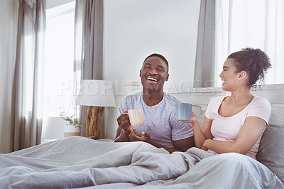 Buy stock photo Shot of a young couple having coffee in bed