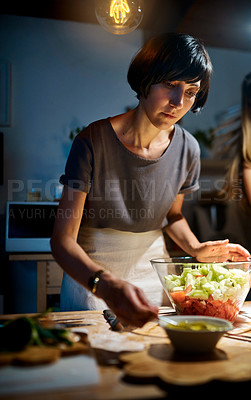 Buy stock photo Shot of a young woman preparing a salad in her kitchen at home