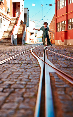 Buy stock photo Full length shot of an attractive young woman walking along the tram lines in the city of Portugal alone