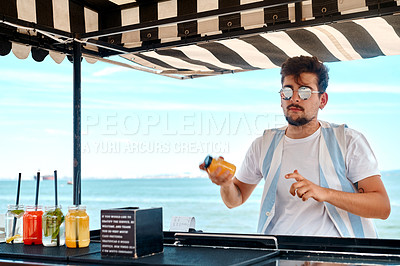 Buy stock photo Cropped shot of a handsome young man standing alone and shaking a bottle of juice along the beach in Portugal