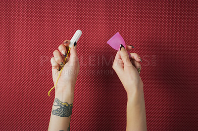 Buy stock photo Studio shot of an unrecognizable woman holding a menstrual cup and tampon against red background