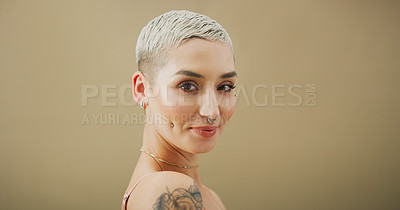 Buy stock photo Studio portrait of an attractive young woman with piercings posing against a brown background