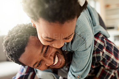 Buy stock photo Closeup of a cheerful young man giving his daughter a piggyback ride inside at home during the day