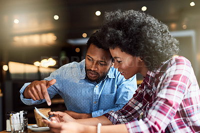 Buy stock photo Shot of two young businesspeople using a digital tablet during their meeting at a coffee shop