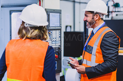 Buy stock photo Cropped shot of two cheerful engineers doing inspection on machinery together inside of a workshop