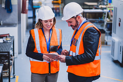 Buy stock photo Cropped shot of two engineers wearing protective gear while having a discussion together inside of a workshop