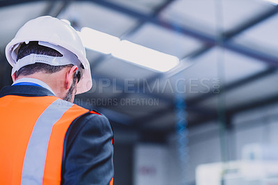 Buy stock photo Rearview shot of a unrecognizable male engineer standing inside of a workshop during the day